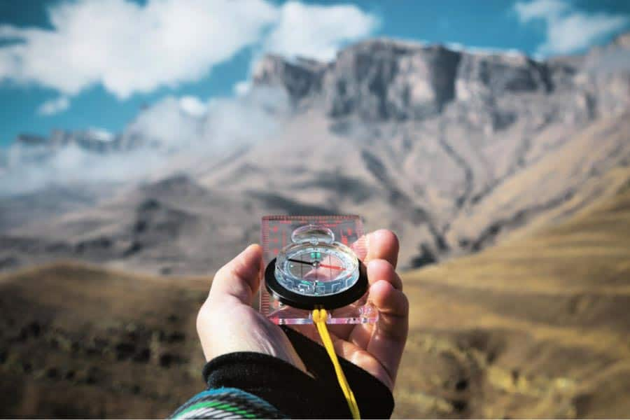 compass pointed towards a mountain for taking the bearing