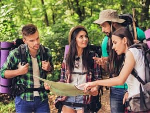 4 young people seeing map in the wilderness
