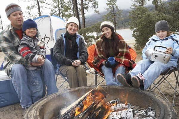 Family sitting around a fire pit or fire ring