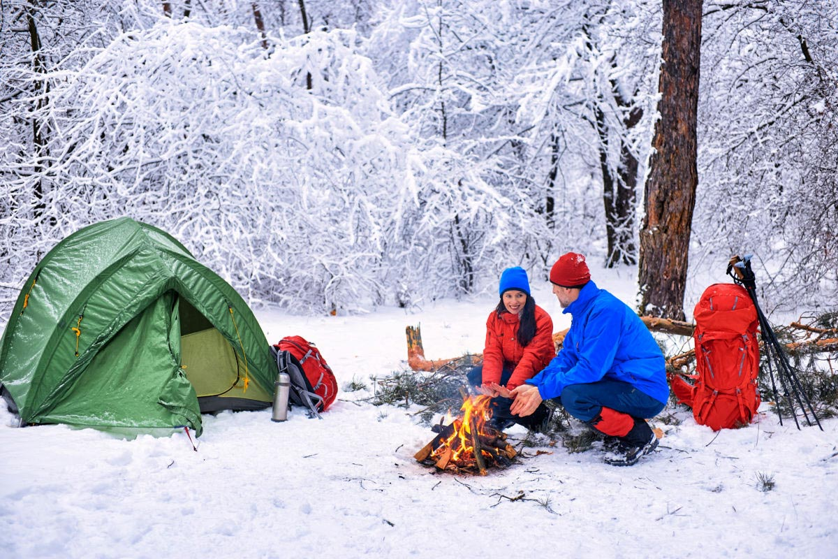 A couple sitting in front of a tent & campfire in extremely cold weather