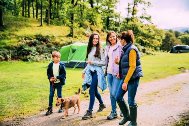 3 ladies and a kid walking in national park with dog lashed