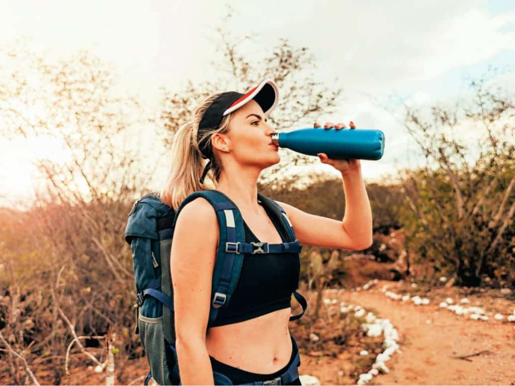 A beautiful female backpacker drinking water