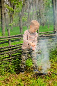 a kid putting off the campfire in the forest