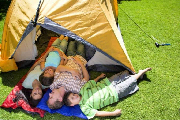 couple with 2 kids sleeping on sleeping bag in the tent