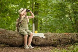a kid with binocular in the wilderness