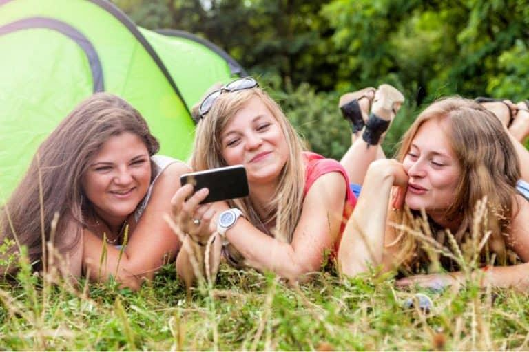 teenage girls having fun on phone lying on grass beside the tent