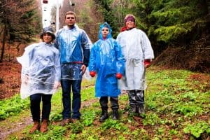 family of 4 wearing rain poncho while standing in the rain