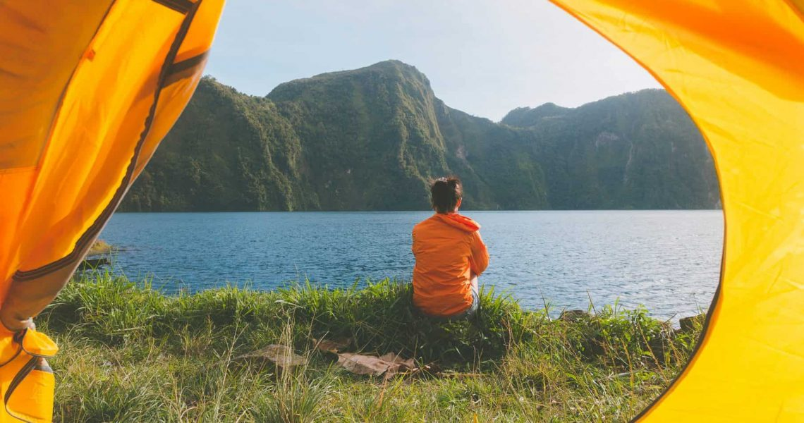 Canva - Person Sitting on Grass Field Facing on Body of Water