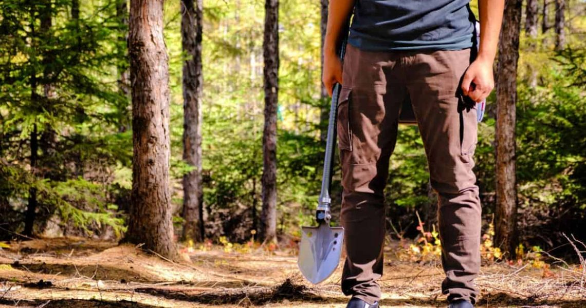 man standing with a camping shovel in the wilderness