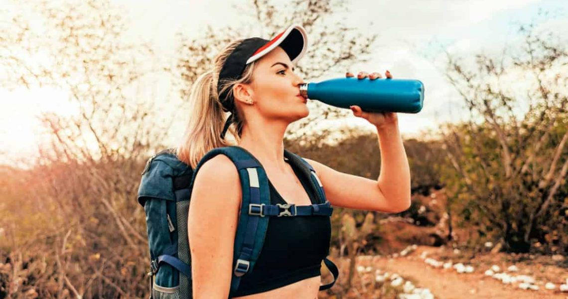 A beautiful female backpacker drinking water
