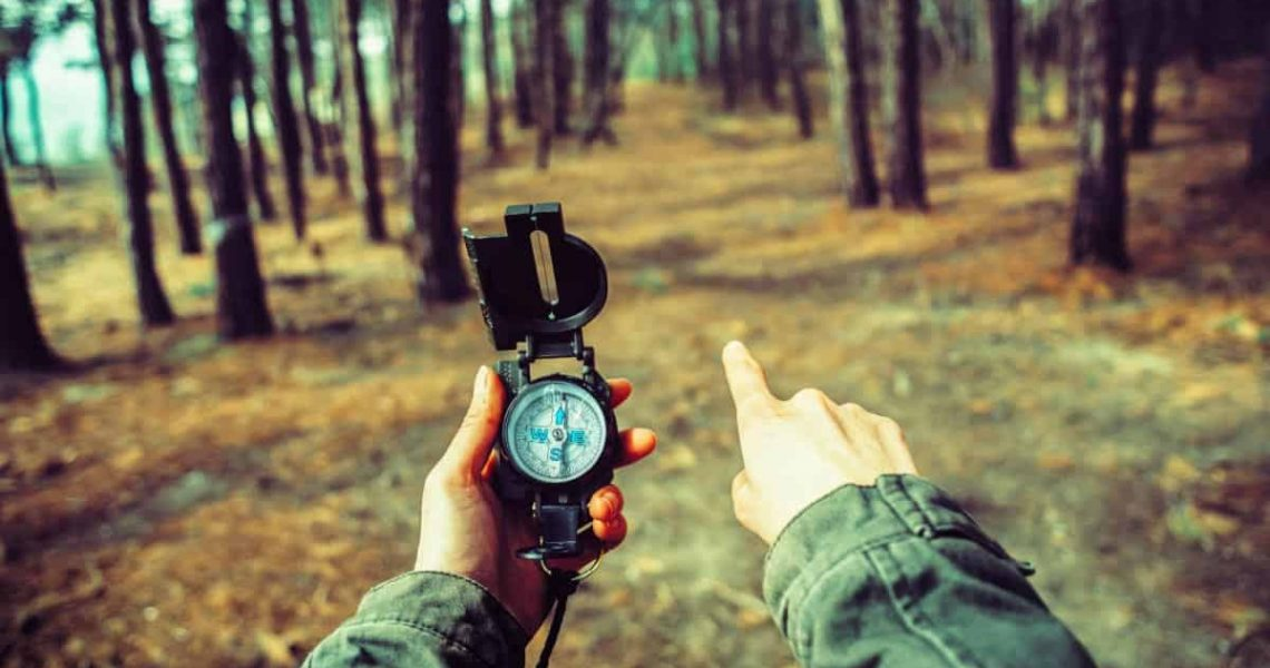 showing direction while compass in another hand
